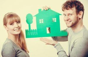 un homme à droite tiens une pancarte verte en forme de maison et haie avec un arbre. Une femme se tiens à gauche de l'image