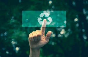 un doigt pointe le symbole de recyclage sous fond vert.