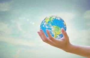 planète terre dans le creux d'une main sous fond de ciel