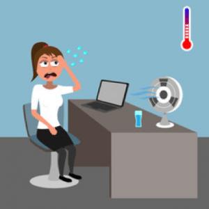 une femme dans son bureau a chaud. Sur son bureau, elle a un ordinateur et un ventilateur.